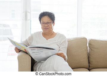 Asian senior woman reading newspaper
