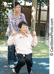 Asian senior women playing swing at outdoor garden park