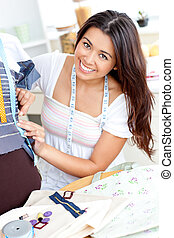 asian sewing smiling at the camera at home