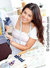 asian sewing smiling at the camera