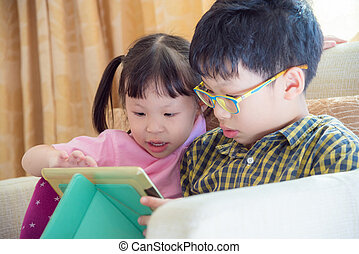 siblings playing games on tablet computer together