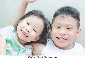 siblings smiling on the floor