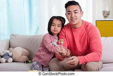 Asian siblings with puppets