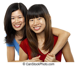 Asian sisters - Two Asian sisters isolated on white...