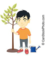 Asian smiling boy  planting a tree.