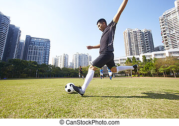 asian soccer football player shoot the ball