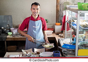 Asian stall waiters stand holding tongs while preparing side...