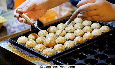 Asian street food. Chicken wings in the form of balls are prepared in a special frying pan. Thailand