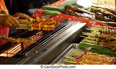 Asian street food. Seller Finished shish kebabs on a wooden skewer with vegetables on the counter