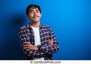 Asian student college wearing a shirt standing with his arms crossed while smiling at the camera