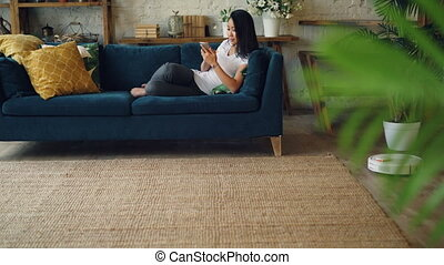 Asian student is using smartphone resting on sofa when...