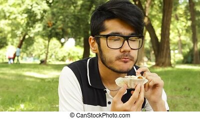 Asian student man eating cupcake sitting in the park