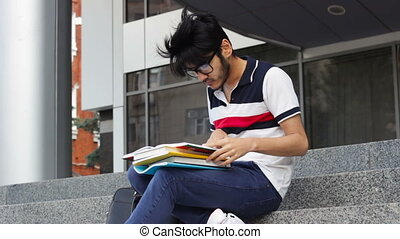 Asian student man sitting on stairs and reading books....