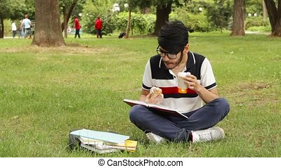 Asian student man studying in the park and drinking coffee...