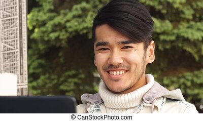 Asian student man working on laptop and smiling in camera