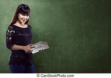 Asian student standing in front of blackboard background