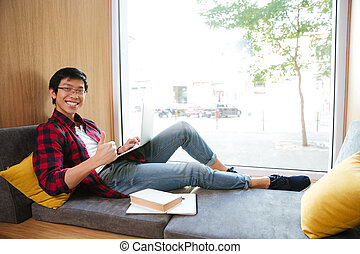 Asian student using laptop in university library sitting on sofa