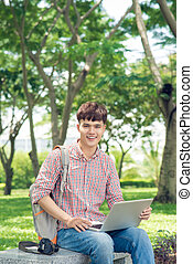 Asian student using laptop sitting in park