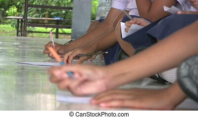 A group of Asian middle school students work on an assignment at a local school in Phuket, Thailand.
