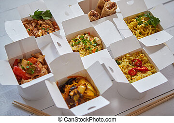 Asian take away or delivery food concept. Paper boxes placed on white wooden table
