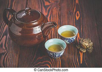 Asian tea set on bamboo mat,Closeup. - Broun ceramic teapot...