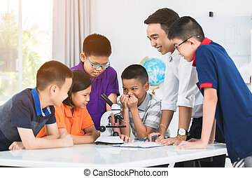 Asian teacher expanding to student in biology class with microscope .