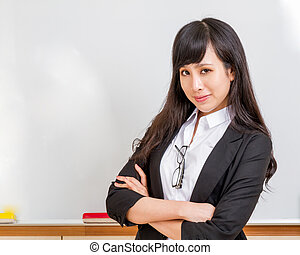 Asian teacher in front of whiteboard smiling - Chinese...