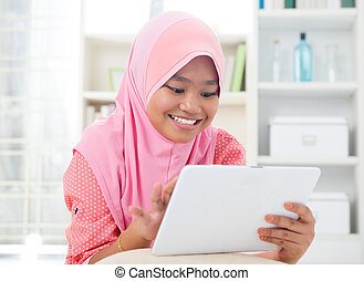 Asian teen using tablet pc computer.