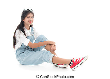 Asian teenage girl smiling and sitting on white background.