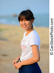 Asian teenager relaxing on the beach with nature light in the mo