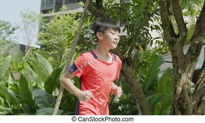 Asian teenager running in garden and jumping in slow motion
