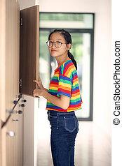 asian teenager standing at school locker looking with eye ...