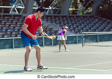 Asian tennis player ready to serve at the beginning of a doubles match