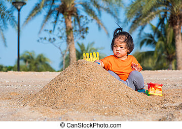 cheerful daughter girl funny digging playing toy with sand