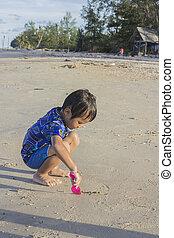 Asian Thai little boy playing sand