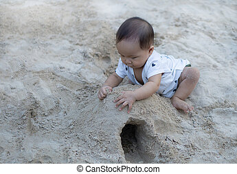 Asian toddler baby thai girl playing with sand in the...