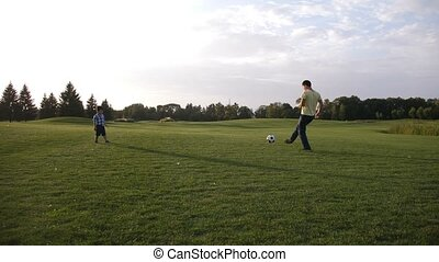 Asian toddler boy playing soccer with his father