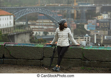 Asian tourist woman with an umbrella in foggy weather on the background of the Dom Luis I Bridge in Porto, Portugal.