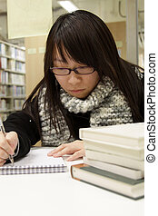 Asian university student in library