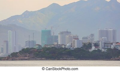 Nha Trang, Vietnam, Asia July 3 2018. Vietnamese holiday resort beach front skyline scene with colourful wooden fishing boats and high rise construction works in progress, panning camera.