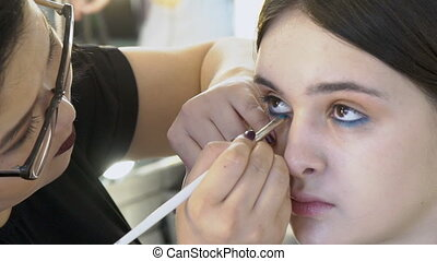 Asian visage artist is doing make-up for young female model in studio, close up.