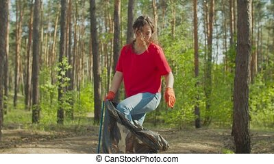 Charming pretty asian woman eco volunteer in protective gloves cleaning forest rubbish and plastic waste, stuffing trash into garbage bag with leg. Environmental conservation and ecology.