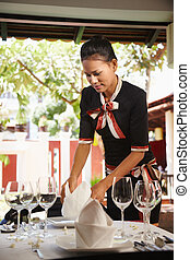 asian waitress setting table in restaurant - Attractive...