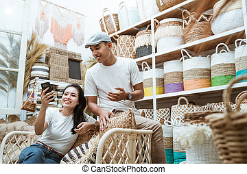 Asian woman and man sit on the sofa using cellphone together