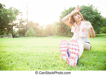asian woman are tired sitting on the lawn.