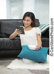 Asian woman at home reading a tablet PC.