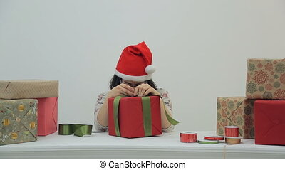 Asian woman at the table with glasses, red cap packs gifts
