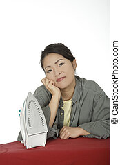 Asian Woman - Beautiful Asian woman ironing clothes on a...