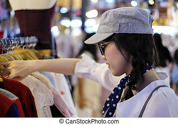 Asian woman choosing clothes in shop