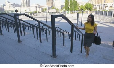 Asian woman climbing stairs in a hurry for work - Gorgeous...